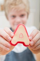 Boy holding unbaked letter biscuit in cutter