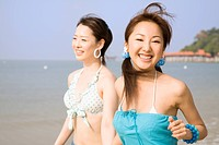 Two young women walking at beach