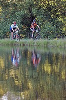 Mountain bikers ride past lake in Pisgah Forest, Western North Carolina, during 24_hour endurance mountain biking race. Reflection shown in water.