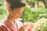Young woman in kimono holding cup
