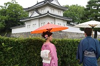 Young couple in kimono looking castle
