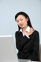 Mid adult businesswoman suffering from pain on shoulder