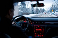 A mid_adult man is driving on snow_covered winter roads in Colorado