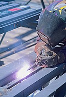 welder welding steel roof sections together