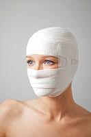 una donna con la testa fasciata da una benda