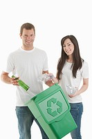 Couple throwing glass and plastic bottles in the recycling bin (thumbnail)
