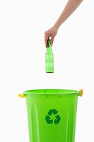 Young woman's arm throwing glass bottle in the recycling bin