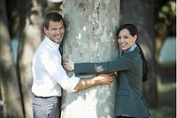 Business people outdoor hugging a tree