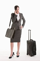 Young woman in suit with wheeled suitcase talking on phone