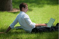 Man sitting in grass with laptop