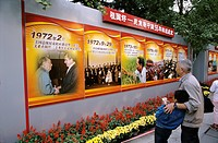 Boy takes notes from billboard timeline of Chinese history, including Mao Zeong and Richard Nixon, Beijing, China