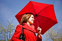 A young woman holding an umbrella, smiling