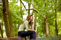A young woman sitting on a log, looking thoughtful