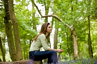 A young woman sitting on a log, smiling