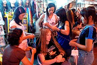Thailand, Bangkok, Thai Hairdressers Braiding the Hair of a Western Tourist on the Street.