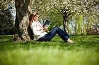 A young woman leaning against a tree, reading a book (thumbnail)