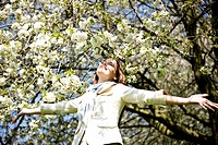 A young woman standing under a tree, arms outstretched (thumbnail)