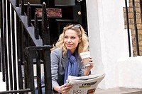 A mid adult woman sitting on steps, holding a coffee and a newspaper