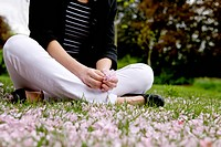 A woman sitting on the grass, holding spring blossom (thumbnail)