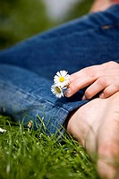 Close_up of a woman holding some daisies