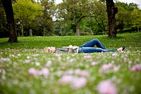 A young woman lying on the grass in springtime