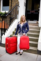 A young woman standing with her suitcases, smiling