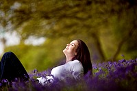 A young woman lying amongst bluebells