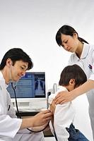 Male doctor and female nurse examining boy