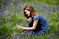 A young woman picking bluebells, smiling