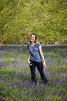 A young woman standing in the woods, holding a bunch of bluebells, laughing