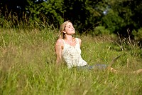 A young woman sitting on the grass with a laptop, enjoying the sun