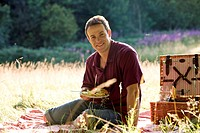 A young man having a picnic, smiling