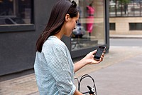 A young woman on a bicycle, looking at a map on her mobile phone