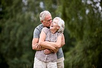 A senior couple standing in a field, laughing (thumbnail)