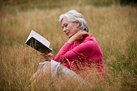 A senior woman sitting on the grass, reading a book
