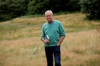 A senior man standing in a field, holding a book