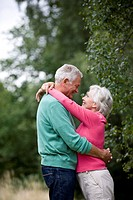 A senior couple standing outdoors, embracing