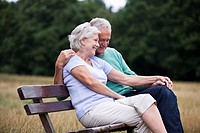 A senior couple sitting on a bench in a park, embracing