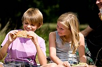 A young boy and girl having a picnic