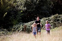 A father and children running in the countryside