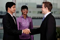 Indian and Caucasian man shaking hands while woman looks on.