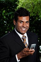 Indian man smiling holding phone