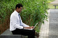 Indian man sitting outside working on laptop with plants in background
