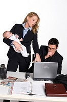 Professional woman in office, holding baby looking at laptop with male colleague