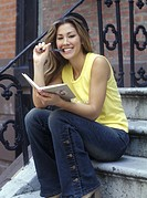 Young woman with book, smiling, portrait