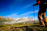Male backpacker views Gulkana Glacier while hiking in the Alaska Range, Southcentral Alaska, Summer/n