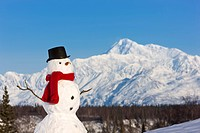 Snowman red scarf and black top hat sitting on a hillside with Mount McKinley in the background, Denali State Park, Southcentral Alaska, Winter