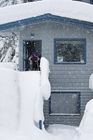 Young skier leaving the house during snowfall to go skiing, Alyeska Resort, Girdwood, Southcentral Alaska, Winter
