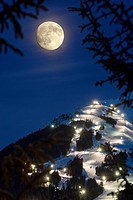 Winter moonrise over Mt. Alyeska during the annual Torchlight Parade, Girdwood, Southcentral Alaska, Winter, COMPOSITE