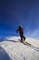 Man backcountry skiing up an icy ridge near Wrangell Peak, Tongass National Forest, Southeast Alaska, Winter